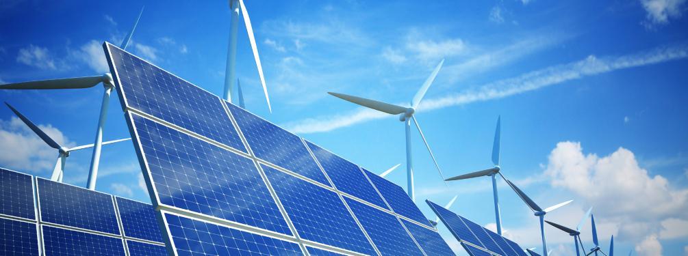 Solaranlagen mit Windrädern vor blauem Himmel